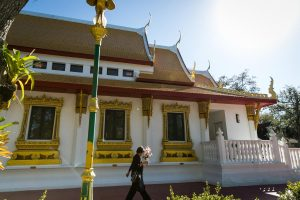 A woman walks outside the Wat Mongkolratanaram, as photographed by NYC photojournalist, Kelly Williams