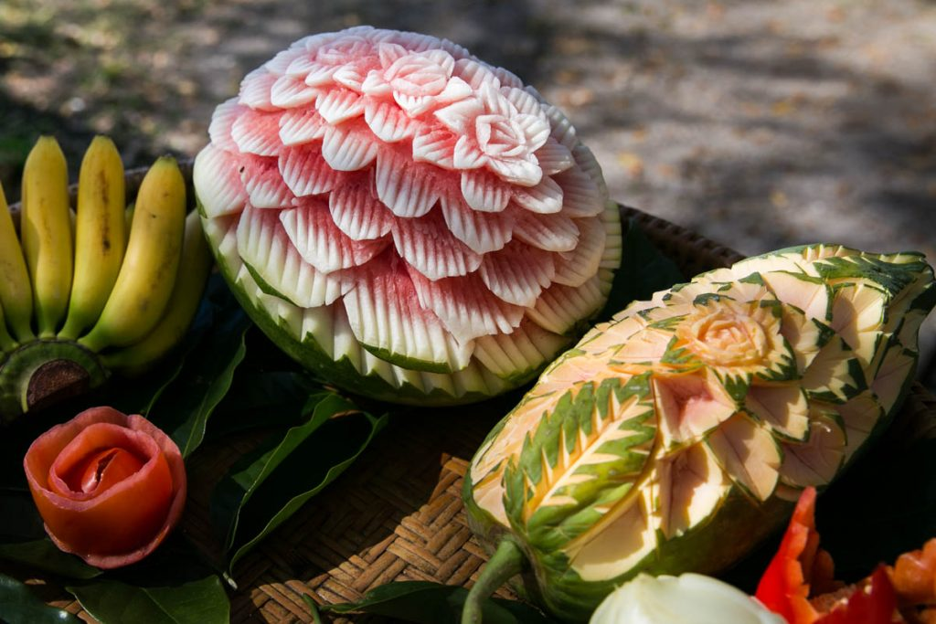 A demonstration of fruit carving at the Wat Mongkolratanaram, photographed by NYC photojournalist, Kelly Williams