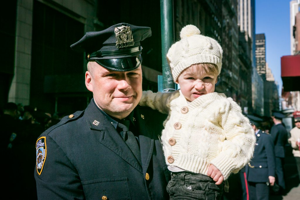 Police officer and boy at the 2016 St. Patrick's Day Parade in NYC by photojournalist, Kelly Williams