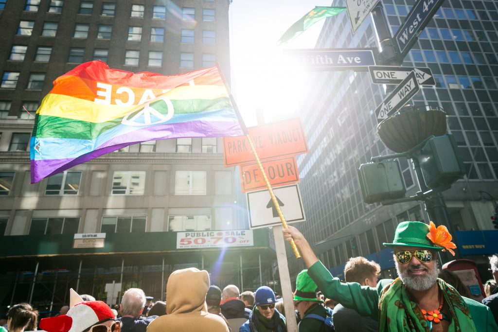 Man waving an LGBT flag at the 2016 St. Patrick's Day Parade in NYC by photojournalist, Kelly Williams