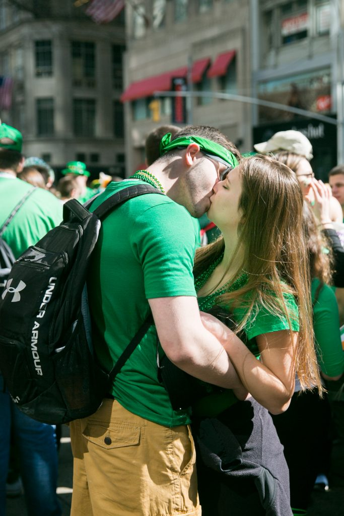 Couple kissing at the 2016 St. Patrick's Day Parade in NYC by photojournalist, Kelly Williams