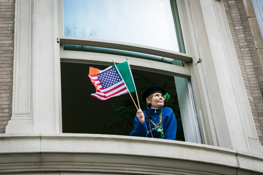 Woman waving flags at the 2016 St. Patrick's Day Parade in NYC by photojournalist, Kelly Williams