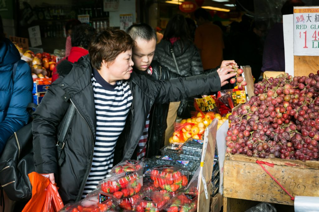Mother and son shopping for fruit in Flushing Queens street photography series