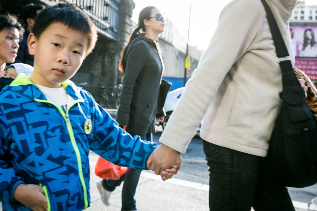 Child and mother walking on the sidewalk in Flushing Queens street photography series