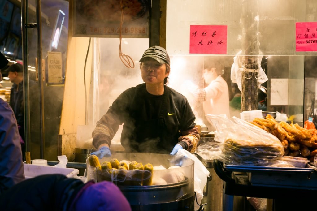 Sidewalk food stall worker in Flushing Queens street photography series