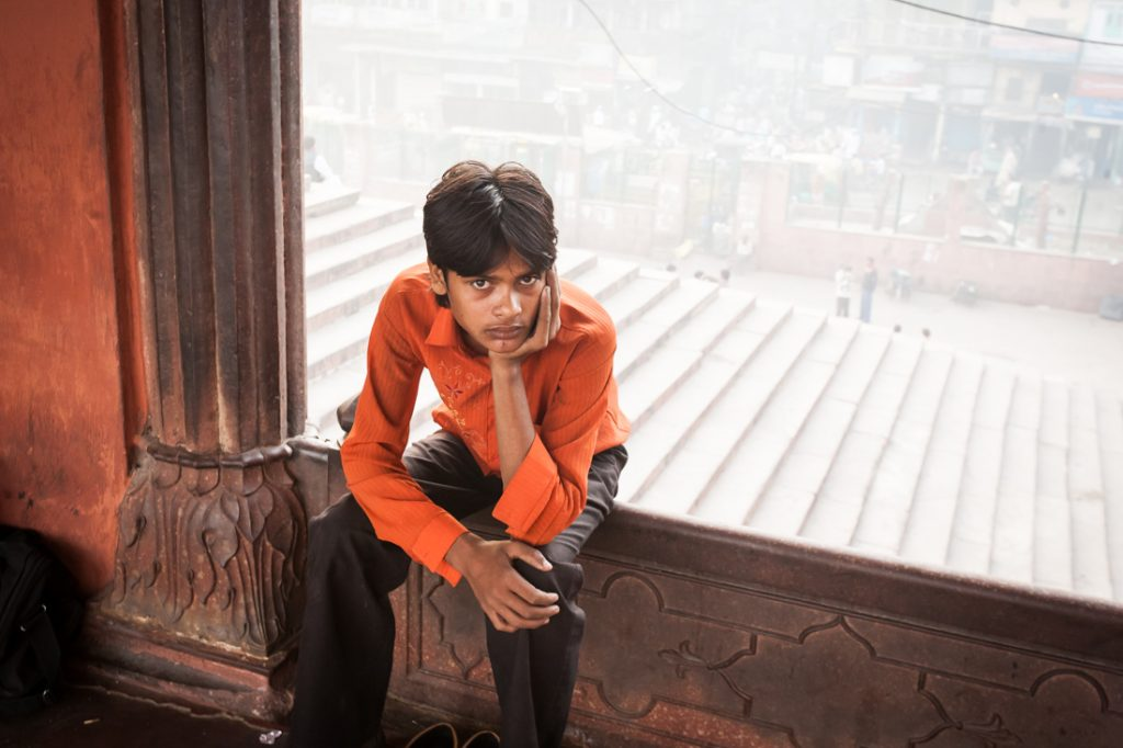 Boy sitting in a window in Delhi, India