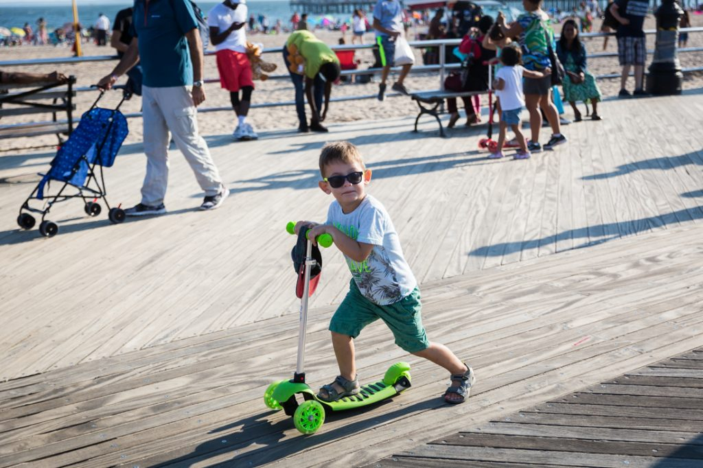 Coney Island street photography of a kid on razor scooter