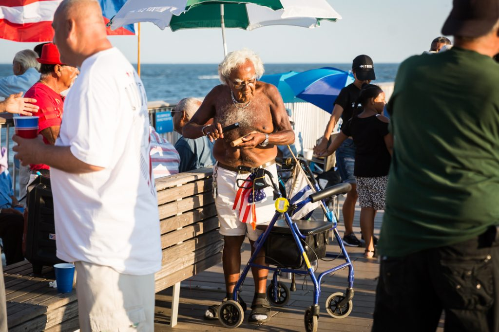 Coney Island street photography of an old man with walker playing music