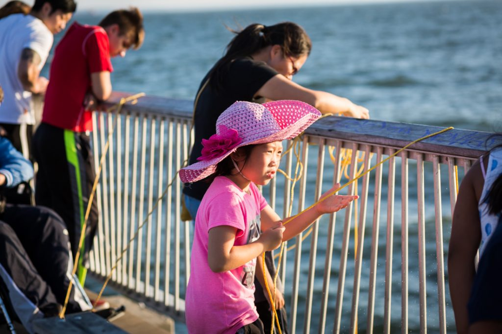 Coney Island street photography of a girl in pink fishing on the pier