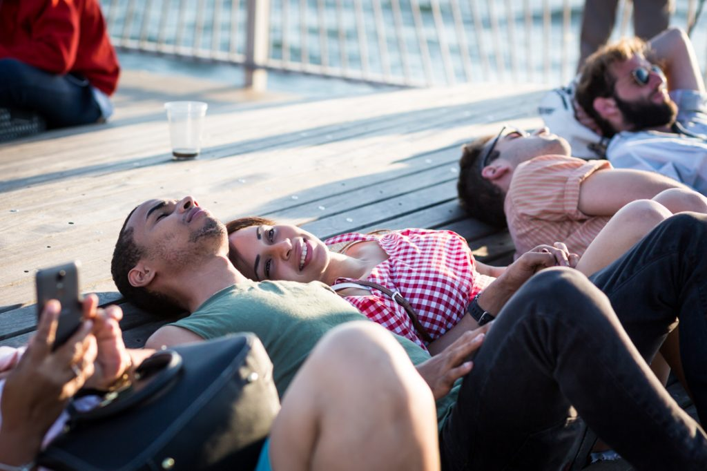 Coney Island street photography of lovers lounging on the pier
