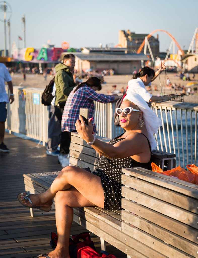 Coney Island street photography of a woman with white turban talking into her phone