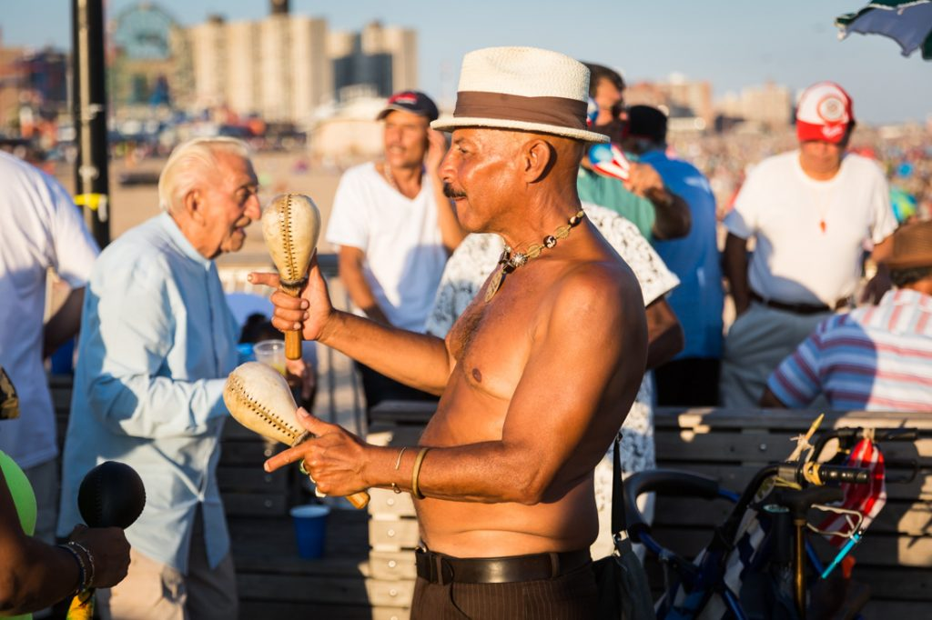 Coney Island street photography of a shirtless man playing maracas