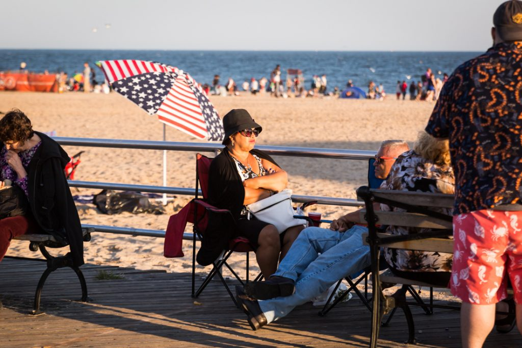Coney Island street photography of a woman wearing a hat on the boardwalk