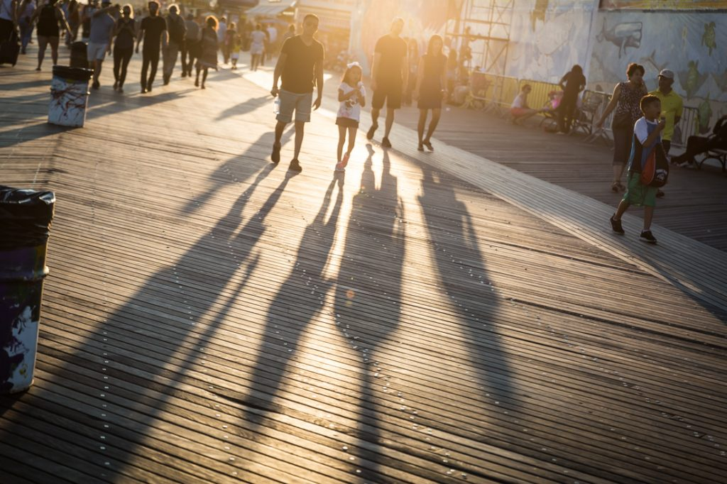 Coney Island street photography of shadows of tourists on the boardwalk