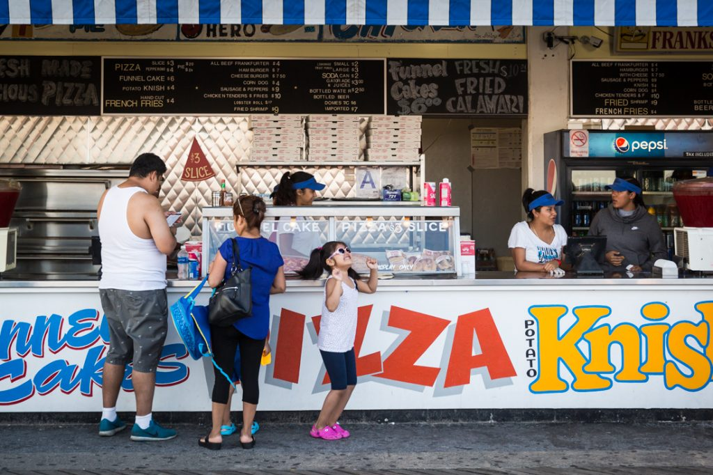 Coney Island street photography of a kid with sunglasses dancing in front of a hot dog stand