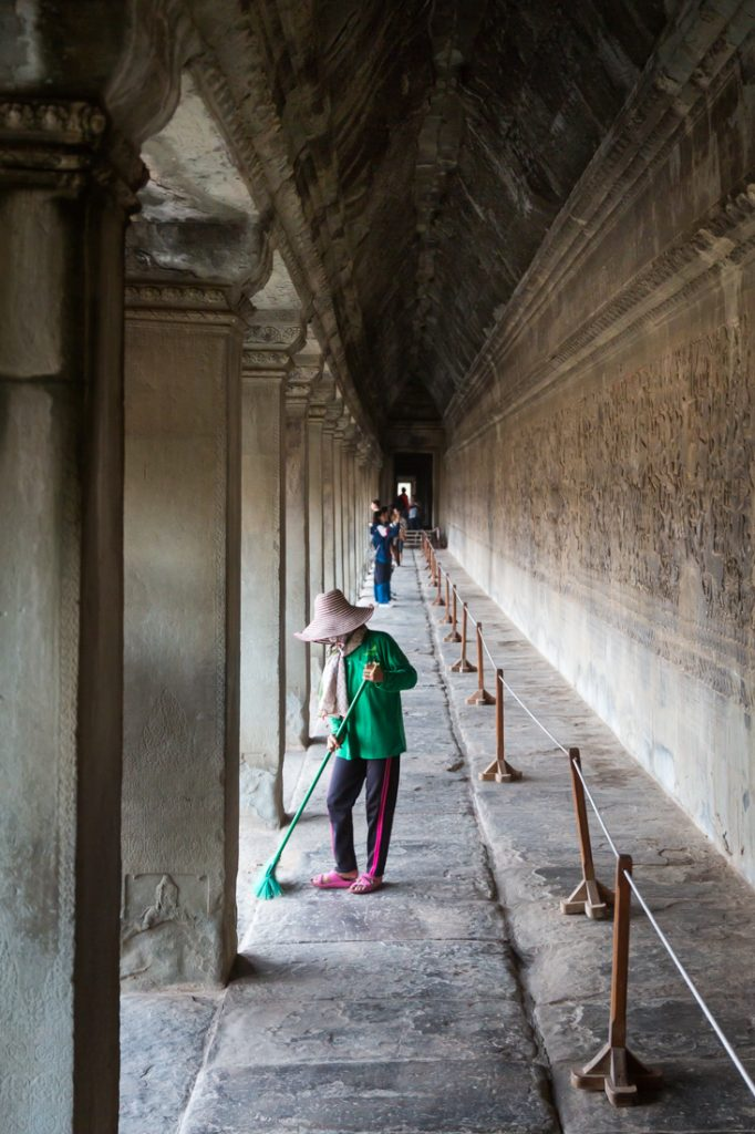 Woman sweeping temple for an Angkor Wat temple guide