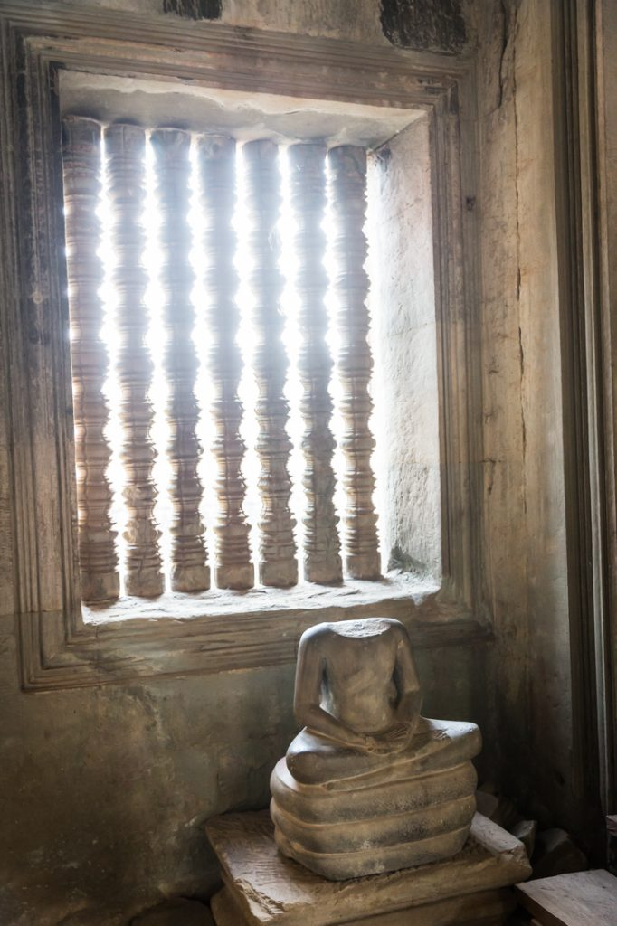 Sun on a headless statue for an article on Angkor Wat travel tips