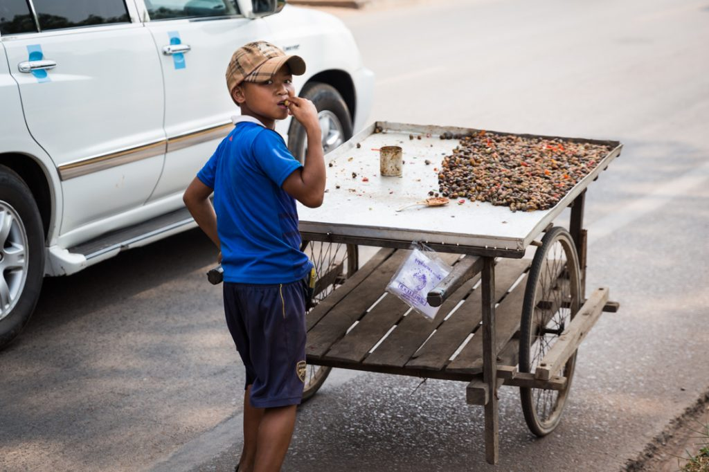 Kid selling seafood for an article on Siem Reap travel tips