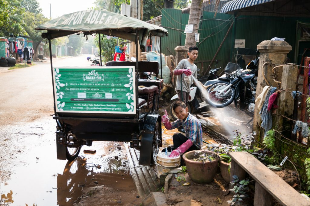 Kid washing tuk tuk for an article on Siem Reap travel tips