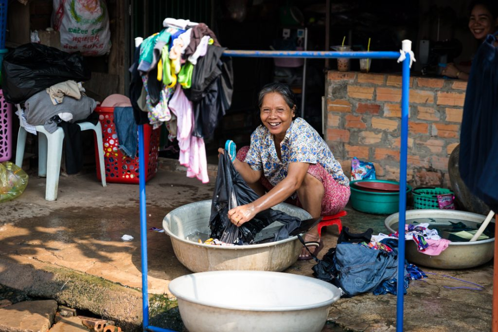 Woman washing clothes for an article on Siem Reap travel tips