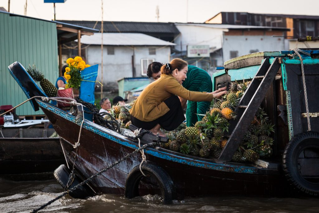 Women sorting pineapples at the Cai Rang Floating Markets