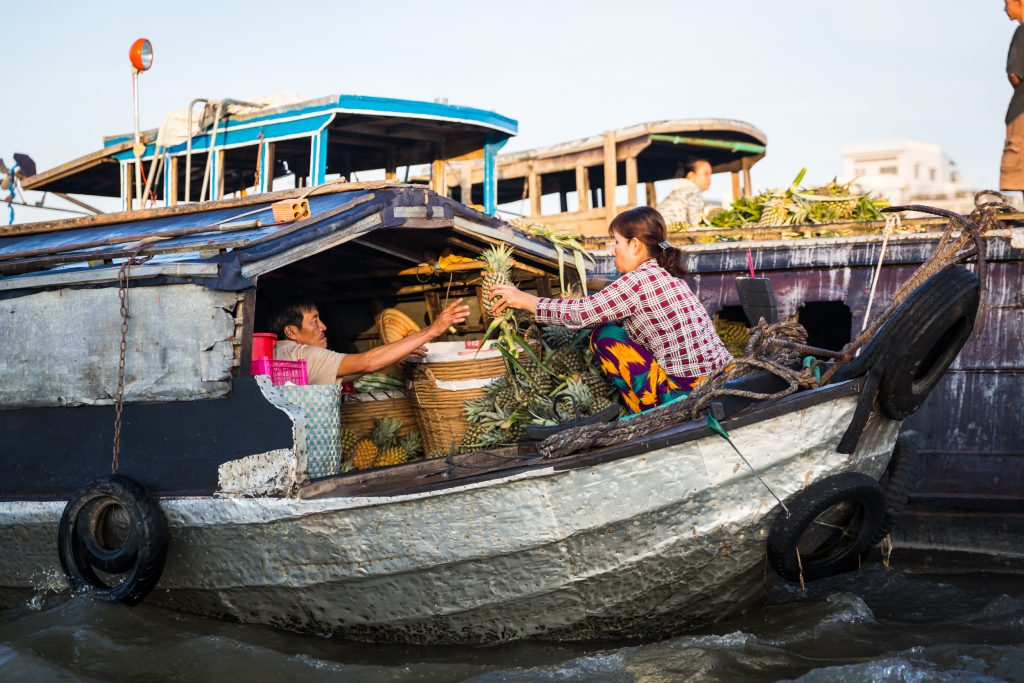 Workers transporting pineapples at the Cai Rang Floating Markets