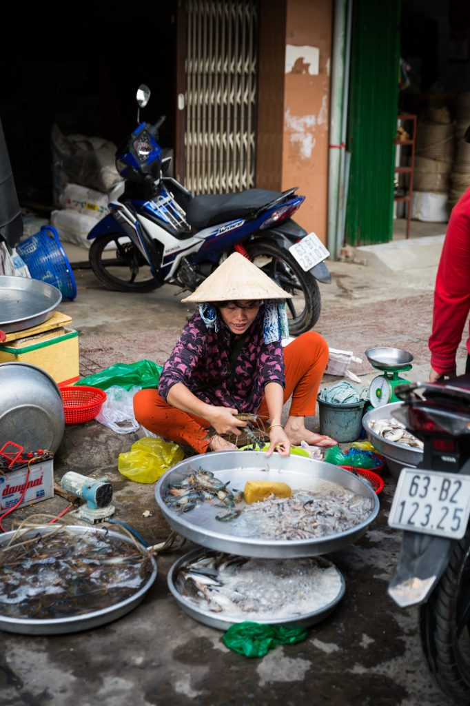 Woman washing fish for an article on the Cai Be Floating Markets