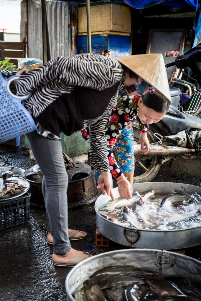 Two women choosing fish for an article on the Cai Be Floating Markets