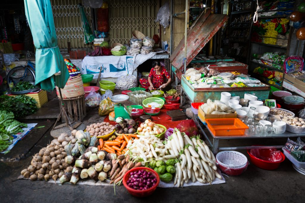 Woman fixing vegetables for an article on the Cai Be Floating Markets