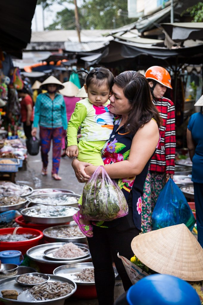 Mother and child at market for an article on the Cai Be Floating Markets
