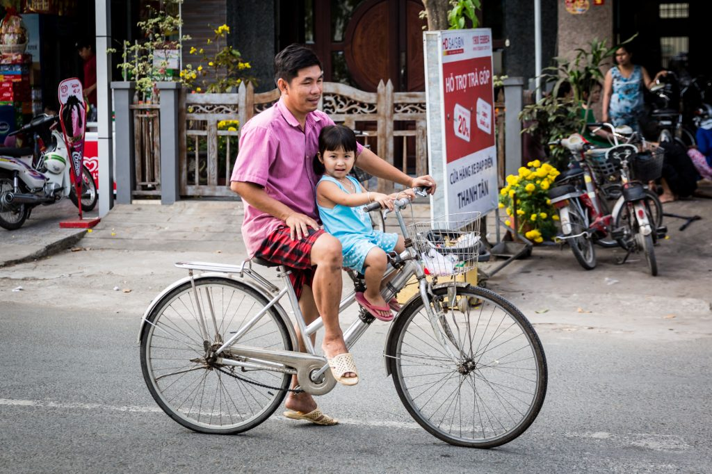 Father and child on bicycle for an article on the Cai Be Floating Markets