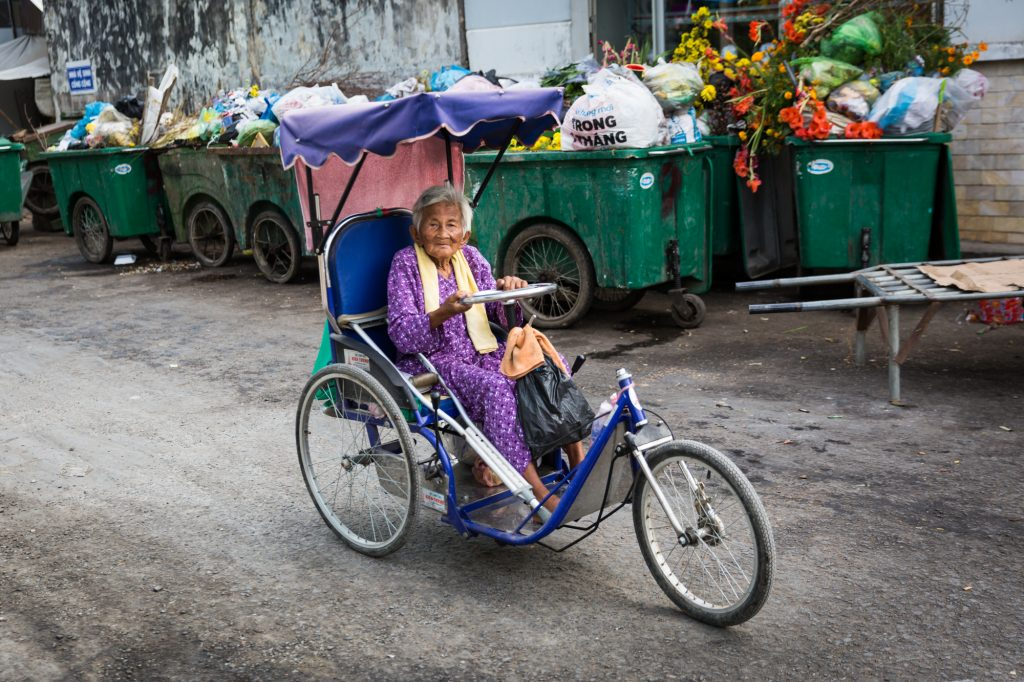Old woman on bike for an article on the Cai Be Floating Markets