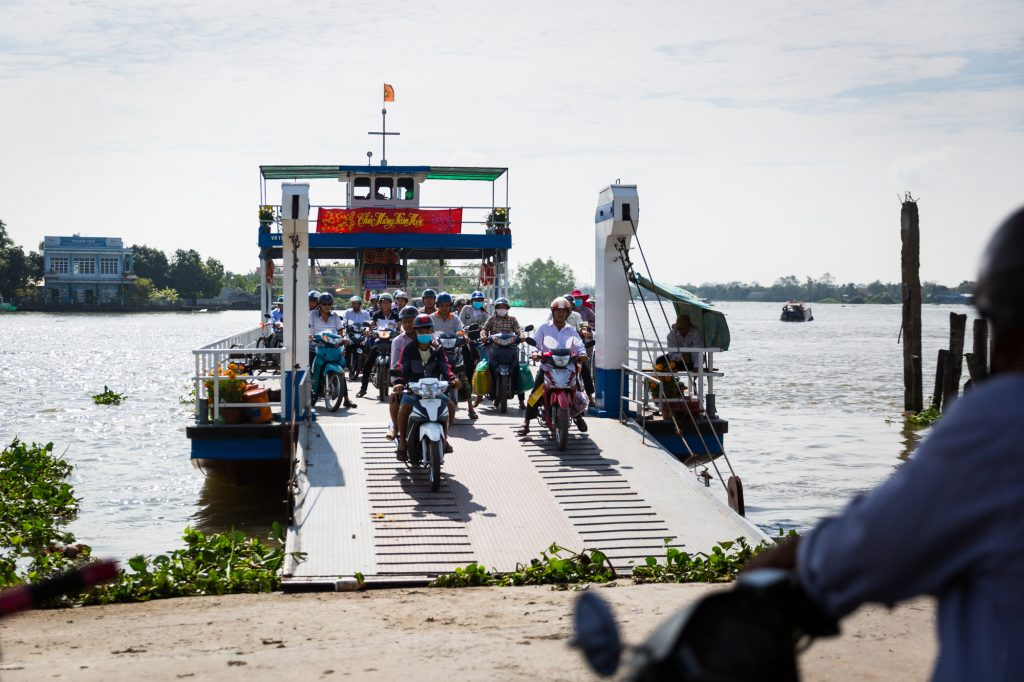 Motorcycles coming off a ferry for an article on the Cai Be Floating Markets