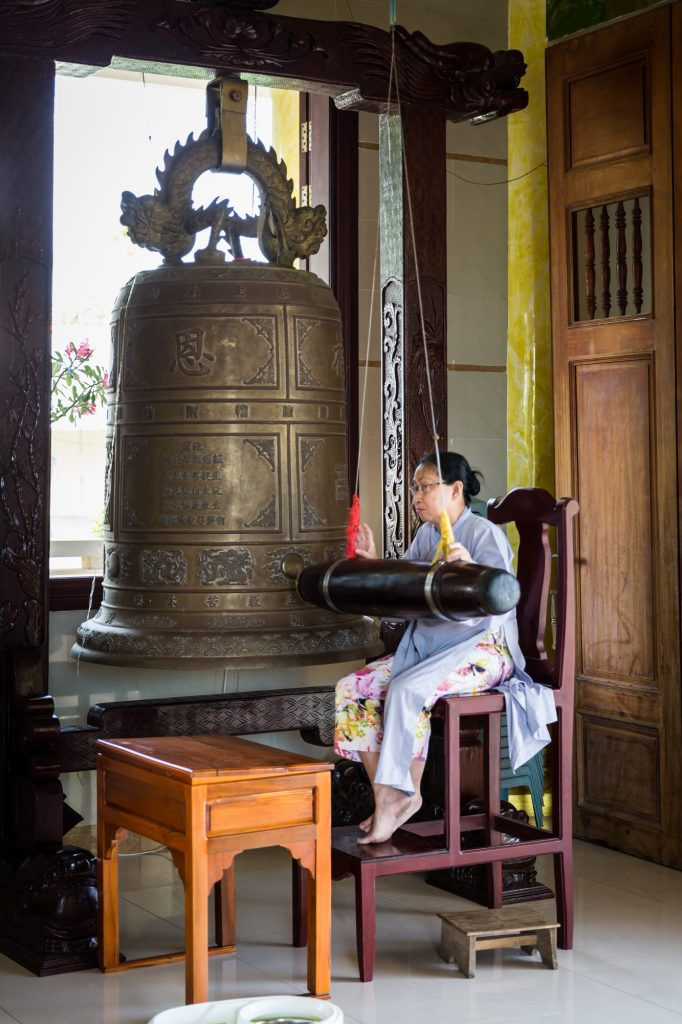 Woman ringing bell for an article on the Cai Be Floating Markets