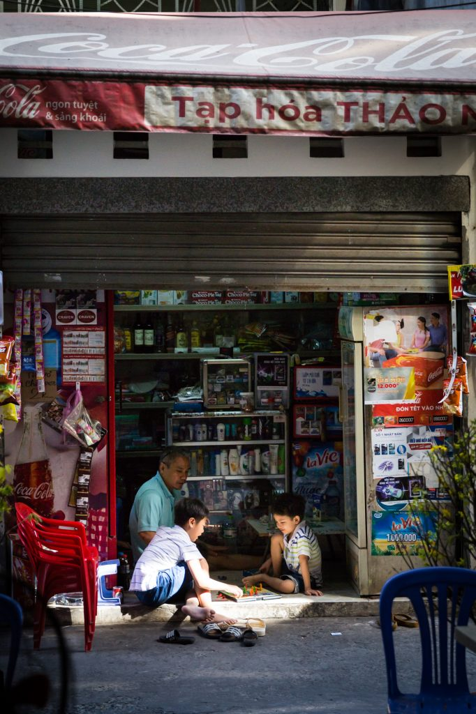 Grandfather and children playing a board game for article on Ho Chi Minh City street photos