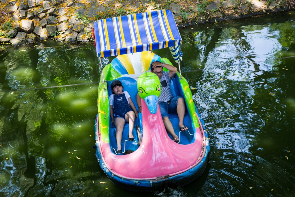 Father and child on paddle boat at the Saigon Zoo and Botanical Garden for article on Ho Chi Minh City street photos