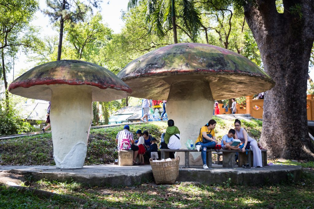 Families sitting under giant mushroom at the Saigon Zoo and Botanical Garden for article on Ho Chi Minh City street photos