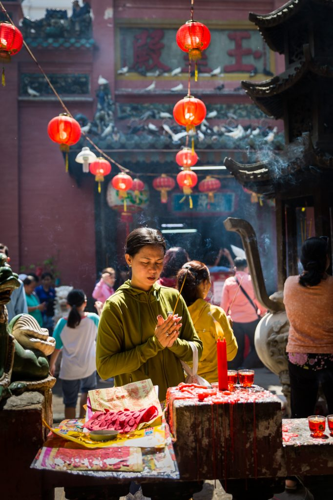 Woman praying at the Ba Thien Hau temple for article on Ho Chi Minh City street photos