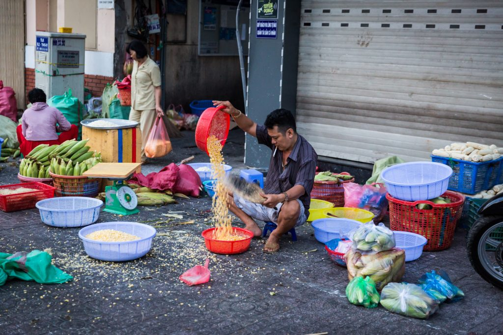 Man pouring rice for article on Ho Chi Minh City street photos