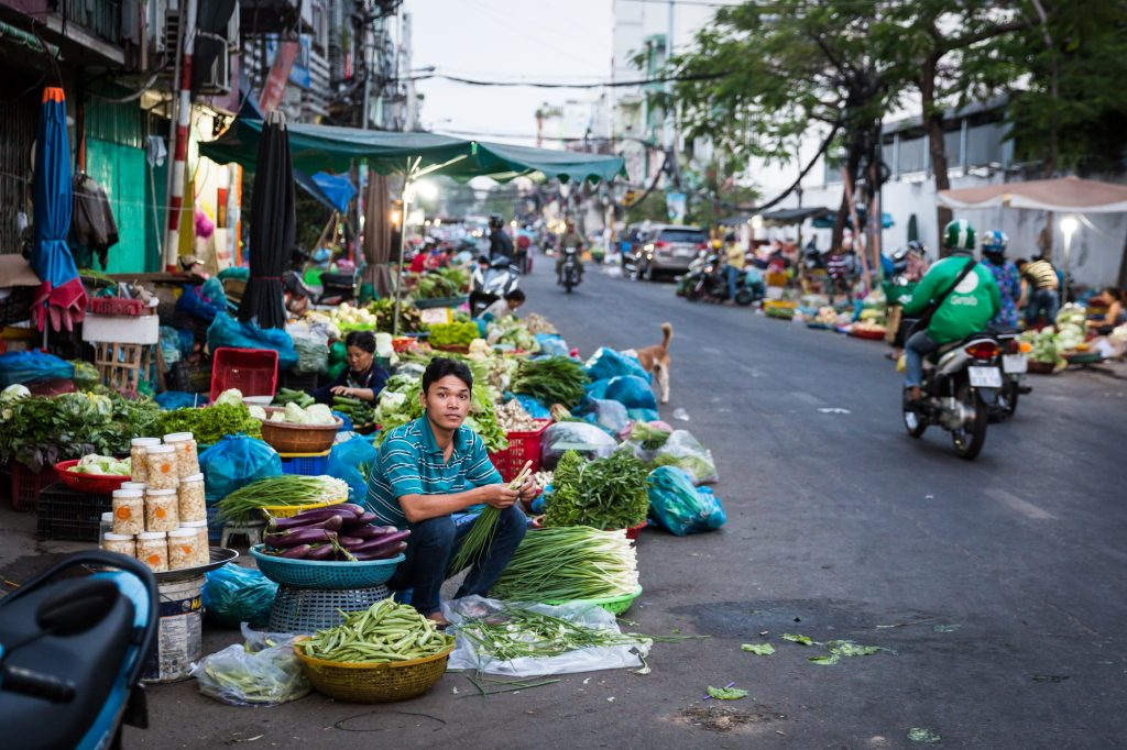 Man selling vegetables in the street for article on Ho Chi Minh City street photos