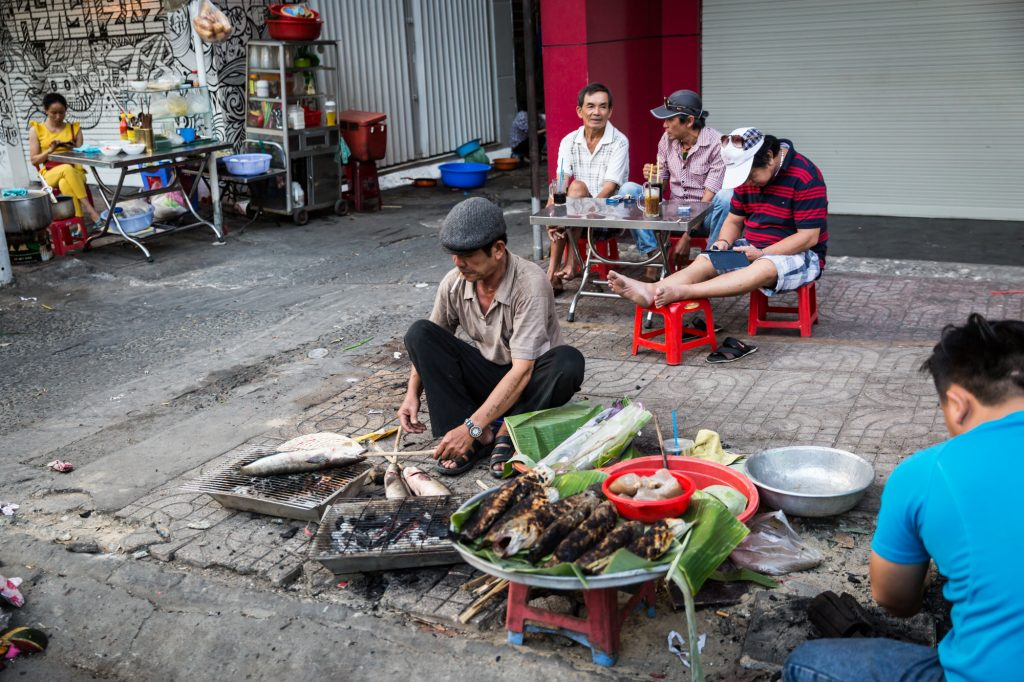 Man preparing fish in the street for article on Ho Chi Minh City street photos