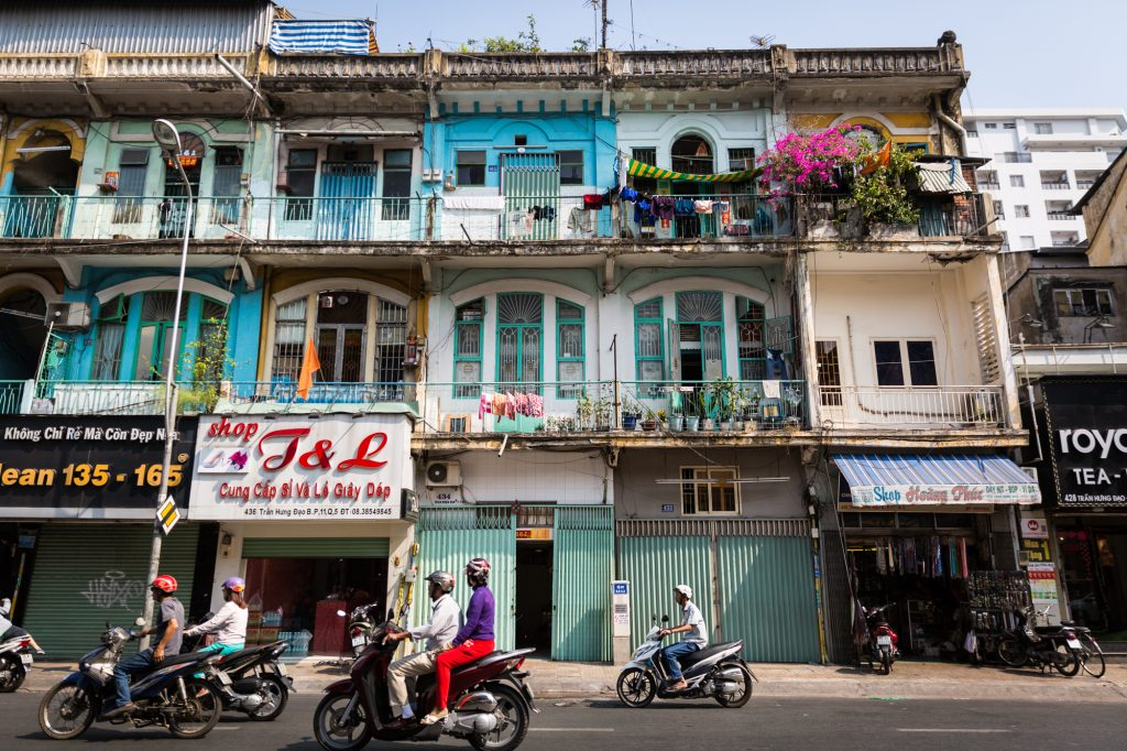 Motorcycles and colorful apartment buildings for article on Ho Chi Minh City street photos