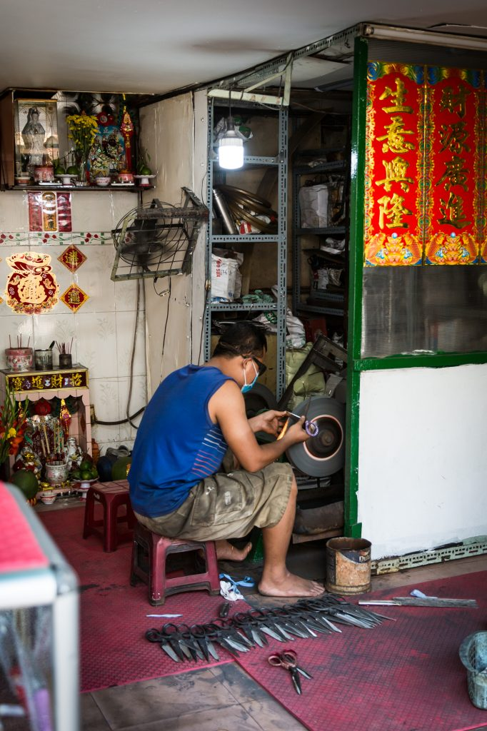 Man sharpening knives for article on Ho Chi Minh City street photos
