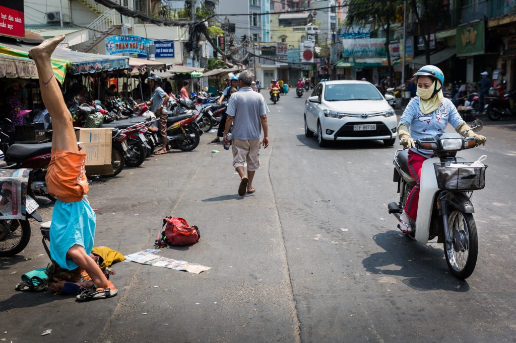 Street performer and motorcyclist for article on Ho Chi Minh City street photos