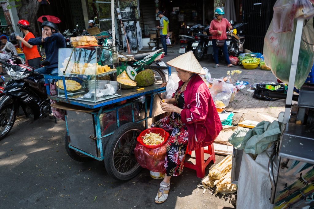 Woman selling fruit in the street for article on Ho Chi Minh City street photos