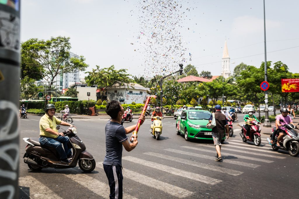 Man exploding a fire cracker in the street for article on Ho Chi Minh City street photos