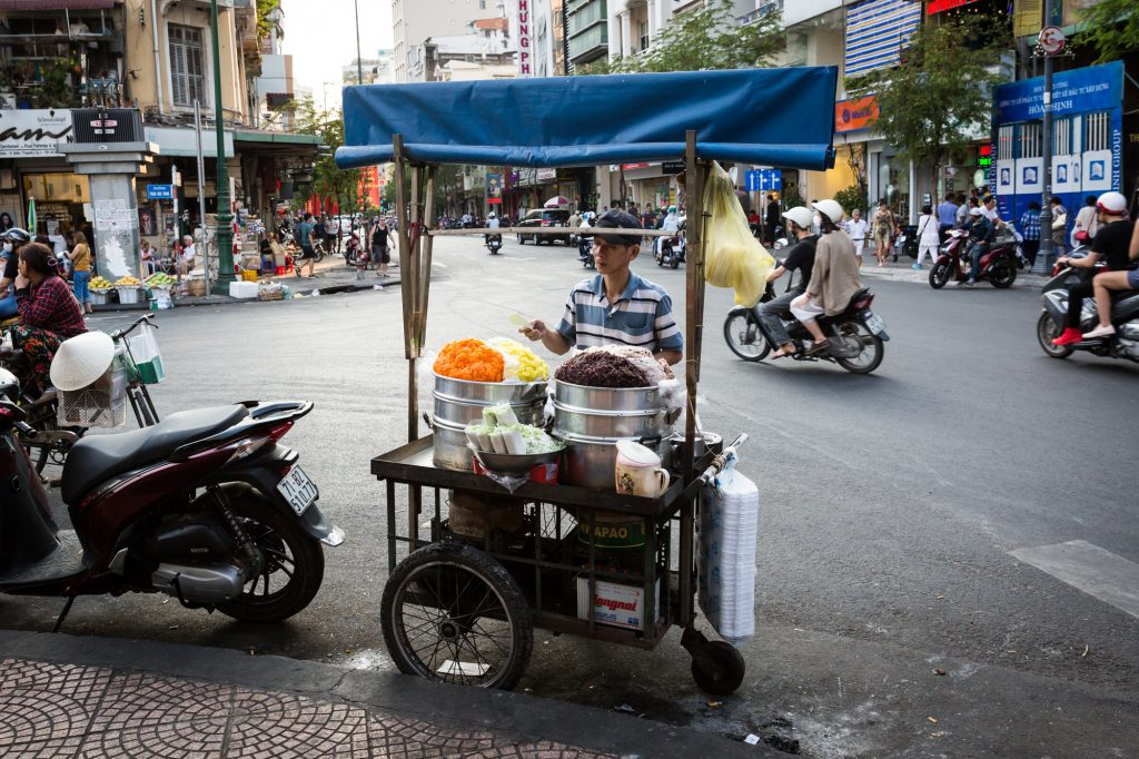 Man selling rice in the street for article on Ho Chi Minh City street photos