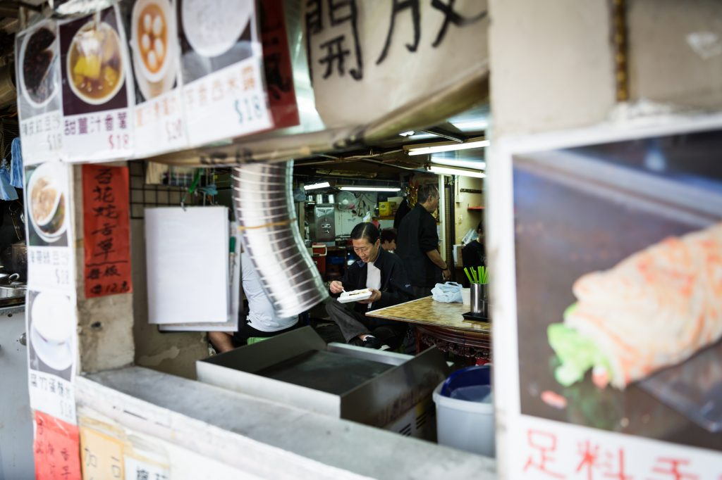 Person eating in a Hong Kong restaurant for a Hong Kong travel guide article