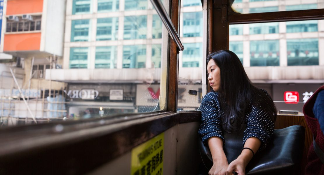 Woman looking out window of Hong Kong ding ding