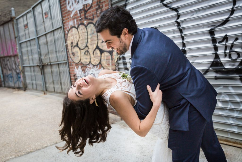 Bride and groom dancing against graffiti wall